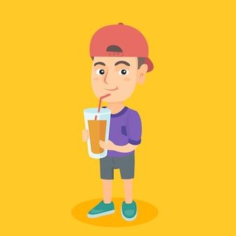 Junge, der orangensaft durch einen strohhalm trinkt.