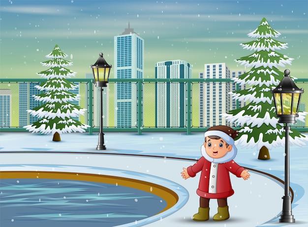 Junge, der warme jacke und hut im park trägt