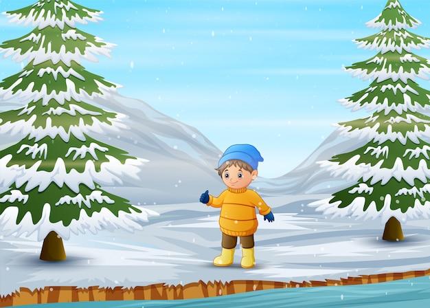 Junge, der warme jacke und hut in der winterzeit trägt