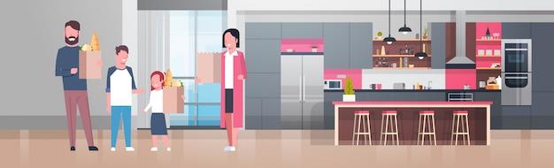 Junge familie, die taschen mit lebensmittelgeschäft-produkten im küchenraum hält