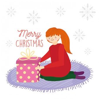 Junge frau der frohen weihnachten auf den knien mit geschenk im teppich