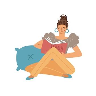 Junge frau, die auf dem boden sitzt und ein buch liest, das konzept nach hause liest, entspannen sich auf dem kissen