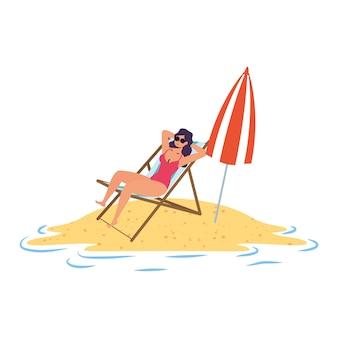 Junge frau, die auf dem strand sitzt, der im stuhl und im regenschirm sitzt