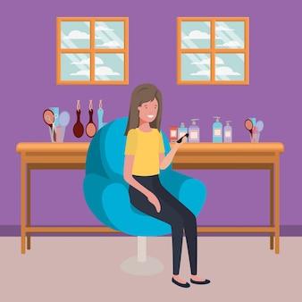 Junge frau, die im salonstuhl unter verwendung des smartphone sitzt