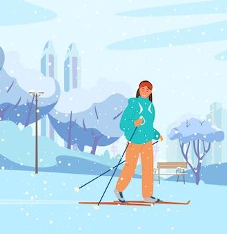 Junge frau, die im winterpark ski fährt. snowy öffentlicher garten mit bank, bäumen, stadtbild am hintergrund.