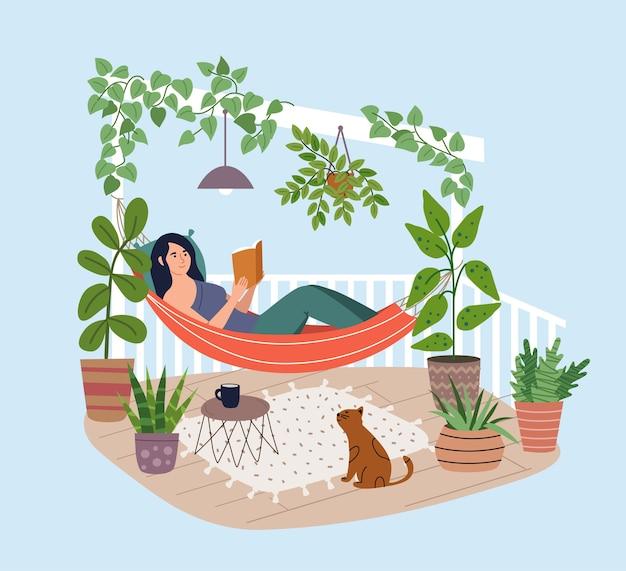 Junge frau, die in der hängematte auf der terrasse entspannt. mädchen, das buch auf dem balkon liest