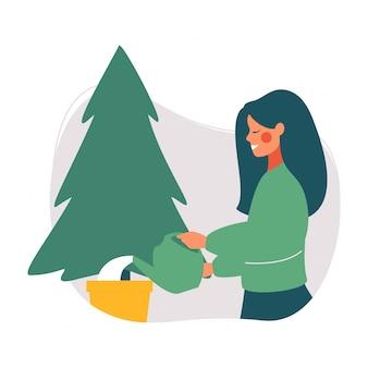 Junge frau, die weihnachtsbaum wässert. weihnachtsbaum wiederverwenden. grünes weihnachtskonzept.