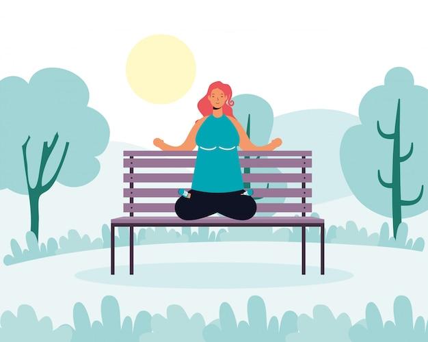 Junge frau, die yoga im parkstuhl praktiziert