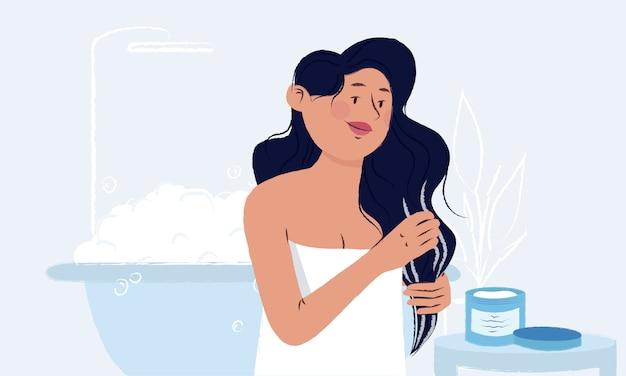 Junge frau gewickelt in ein handtuch in ihrem badezimmer, das maske vom glas auf ihrem nassen langen haar nach dem duschen aufträgt.