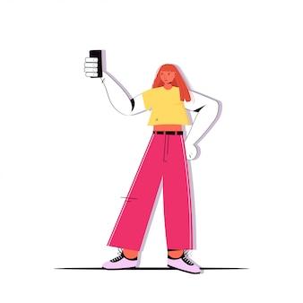 Junge frau in freizeitkleidung, die selfie-foto auf smartphone-kamera macht