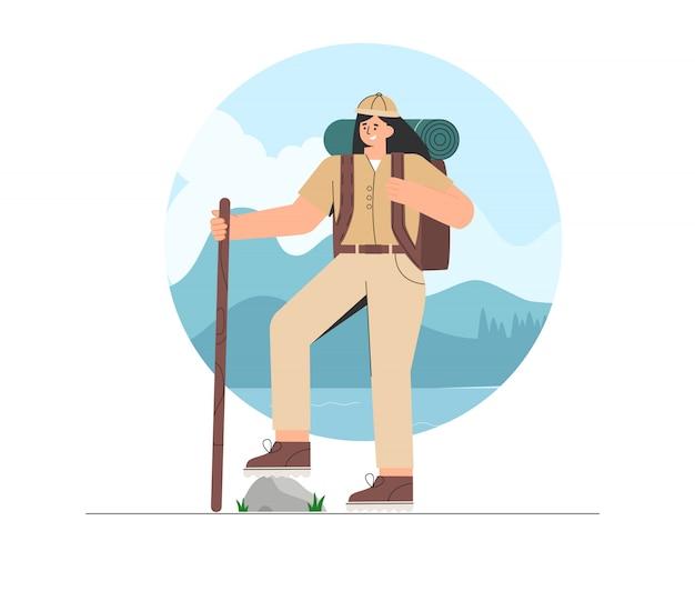 Junge frau in wanderkleidung und rucksack, stehend auf naturhintergrund