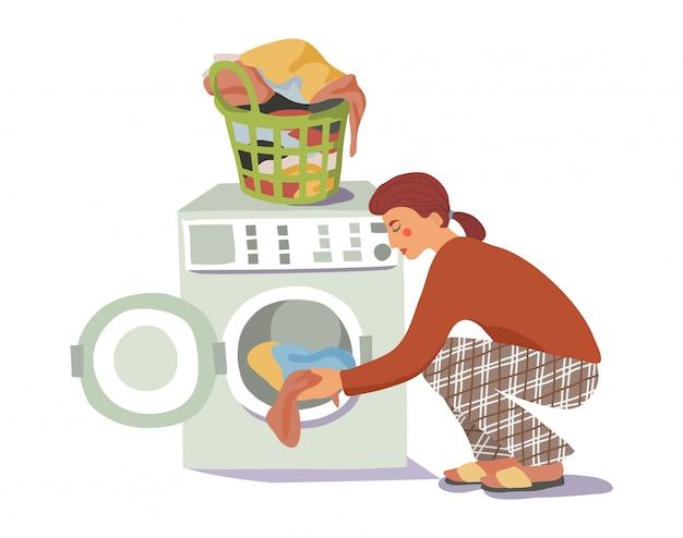 Junge frau lädt die schmutzige wäsche in die waschmaschine