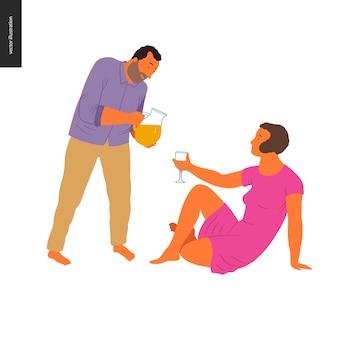 Junge frau sitzt auf dem boden und hält ein glas und einen mann stehen und gießt limonade in das glas