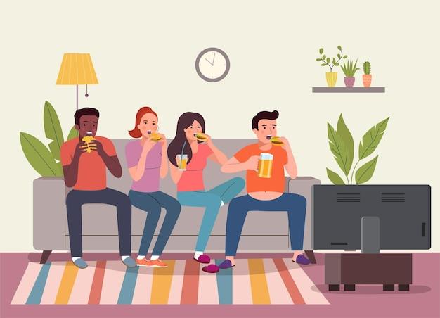 Junge frauen, männer, die auf dem sofa sitzen und burger essen und auf dem sofa im wohnzimmer fernsehen