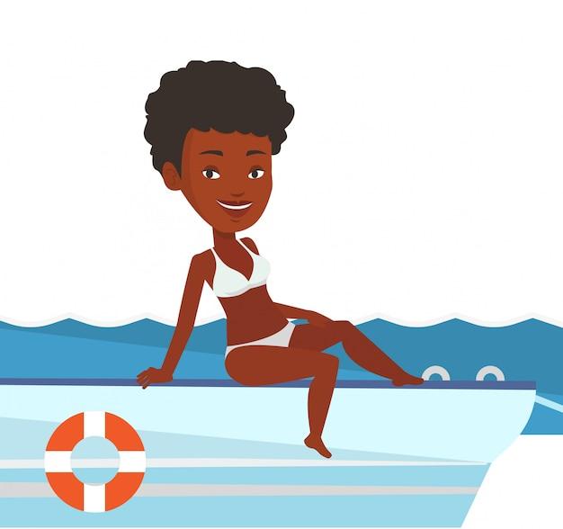 Junge glückliche frau, die auf segelboot bräunt.
