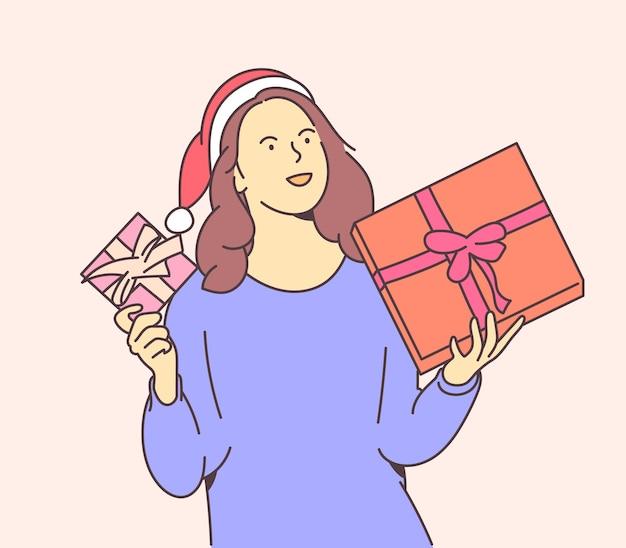 Junge glückliche frau gekleidet in weihnachtsmütze hält kisten mit weihnachtsgeschenken