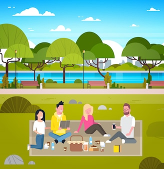 Junge gruppe freund-wochenenden-picknick in den park-leuten, die draußen auf dem entspannenden gras sitzen
