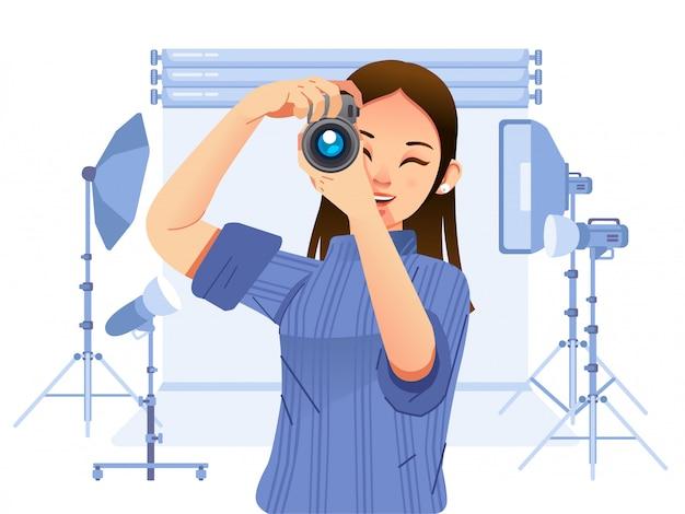 Junge hübsche fotografin, die ein bild mit digitalkamera im professionellen studio mit vielen ausrüstungsillustrationen macht. wird für poster, website-bilder und andere verwendet