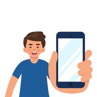 Junge im casual-modus zeigt smartphone-display