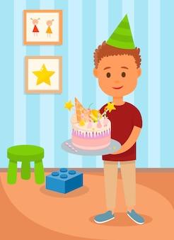 Junge im geburtstags-hut, der kuchen im kinderraum hält.
