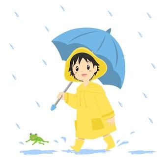 Junge im gelben regenmantel und im halten eines blauen regenschirmes