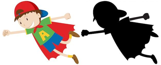 Junge im heldenkostüm mit seinem umriss und der silhouette
