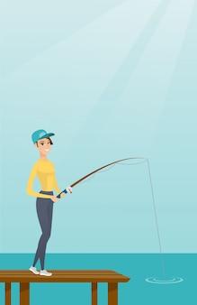 Junge kaukasische frau, die auf anlegestelle fischt