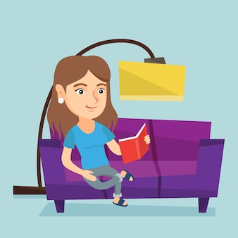 Junge kaukasische frau, die ein buch auf sofa liest.