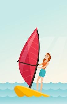 Junge kaukasische frau, die im meer windsurfing ist
