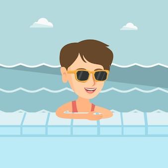 Junge kaukasische frau, die im swimmingpool sich entspannt.