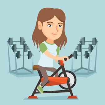 Junge kaukasische frau, die stationäres fahrrad fährt.