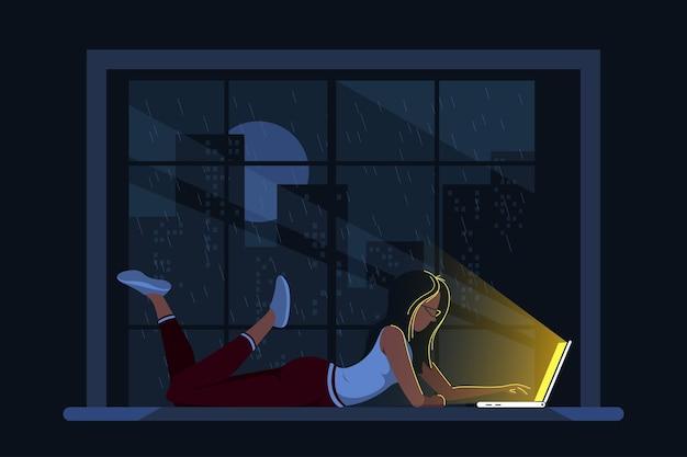Junge kaukasische frau zu hause, die auf der fensterbank liegt und am computer arbeitet. fernarbeit, home office, selbstisolationskonzept. flache artillustration