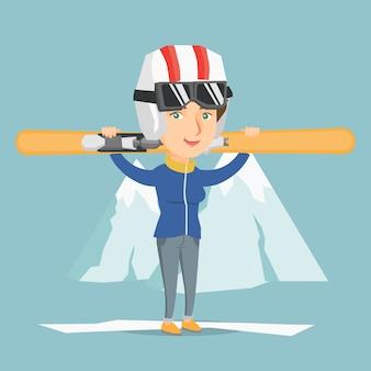 Junge kaukasische sportlerin, die skis hält.