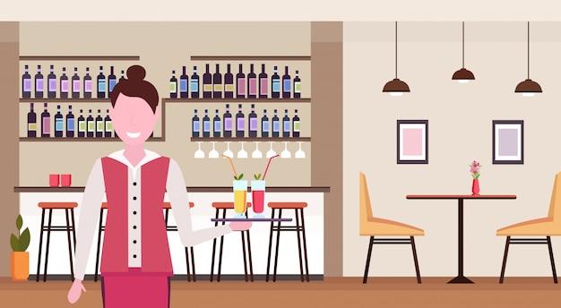 Junge kellnerin hält tablett mit cocktails professioneller arbeiter im café, das getränke für kundenfrau in uniform steht, die im modernen restaurantinnenporträt horizontal stehen