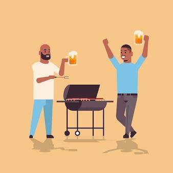 Junge kerle, die fleisch auf grillmännern vorbereiten, die bier afroamerikanische freunde trinken, die spaßpicknick-grillpartykonzept flache volle länge haben