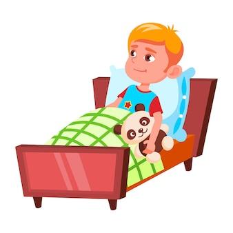Junge, kind, das für den schlaf im schlafzimmer vektor vorbereitet. kaukasischer kleiner schüler, der mit teddybär im bett liegt und zum schlafen im schlafzimmer bereit ist. charakter-freizeit-flache cartoon-illustration