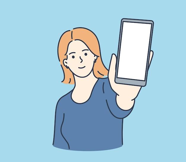 Junge lächelnde frau, die smartphone-bildschirm mit weißem modell für text oder beschriftung zeigt