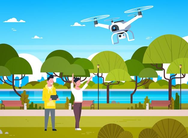 Junge leute, die mit brummen-hubschrauber im park-mann und in frau verwendet fernbedienung für quadrocopter spielen