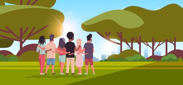 Junge leute gruppe, die rückansicht männer frauen umarmt freundschaftstag feier freunde, die spaß sonnenuntergang landschaft umarmen