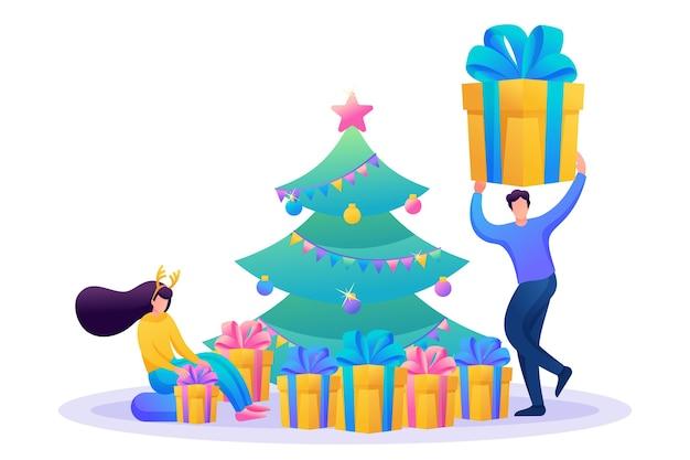 Junge leute haben spaß in der nähe des weihnachtsbaumes und packen geschenke aus.
