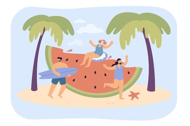 Junge leute mit riesiger wassermelone am strand