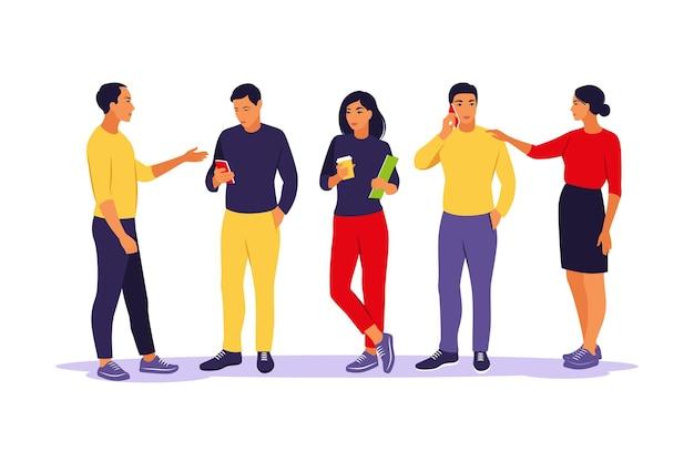 Junge leute stehen und reden miteinander und telefonieren. kommunikations- und diskussionskonzept. isolierte wohnung.