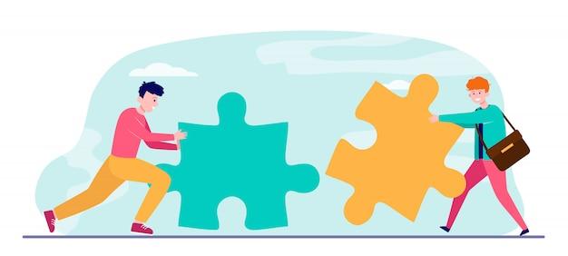 Junge männer mit großen puzzleteilen