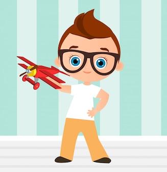 Junge mit brille und spielzeugflugzeug. junge spielt mit dem flugzeug.
