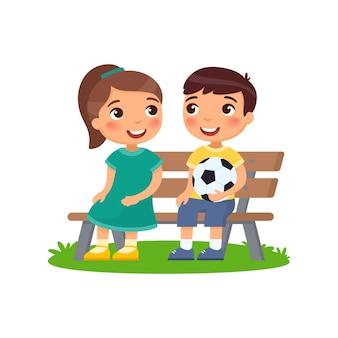 Junge mit fußball und mädchen auf bank