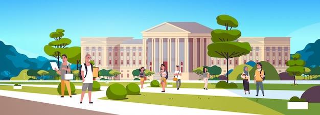 Junge mix-race-studentengruppe auf dem campus yard education college-freunde, die sich entspannen und vor dem äußeren des universitätsgebäudes spazieren gehen