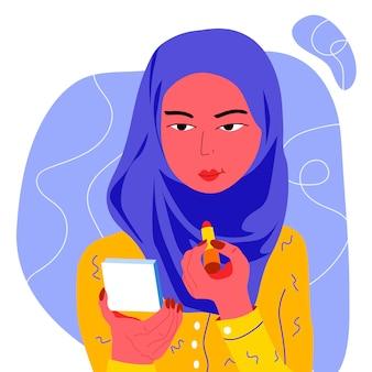Junge moslemische frau, die make-up tut.