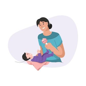 Junge mutter, die spielzeug mit ihrem neugeborenen baby spielt