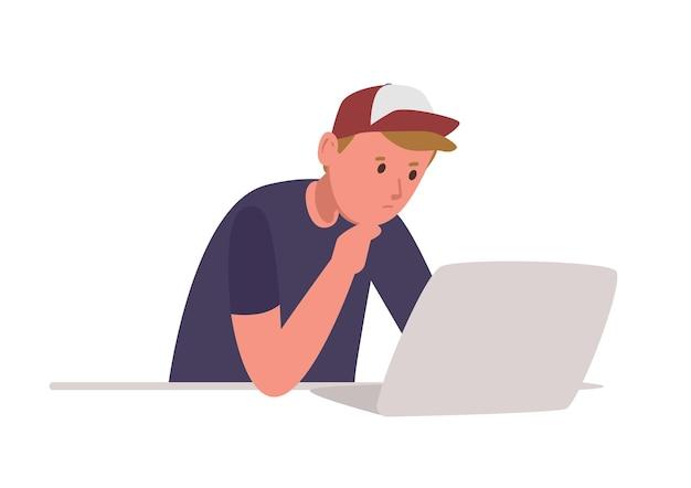 Junge nachdenkliche junge sitzt am laptop-computer und lernt hart isoliert auf weiß
