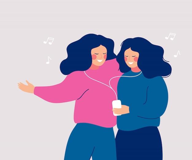 Junge nette frauen, die ihren kopfhörer teilen und musik mit handy und tanzen hören